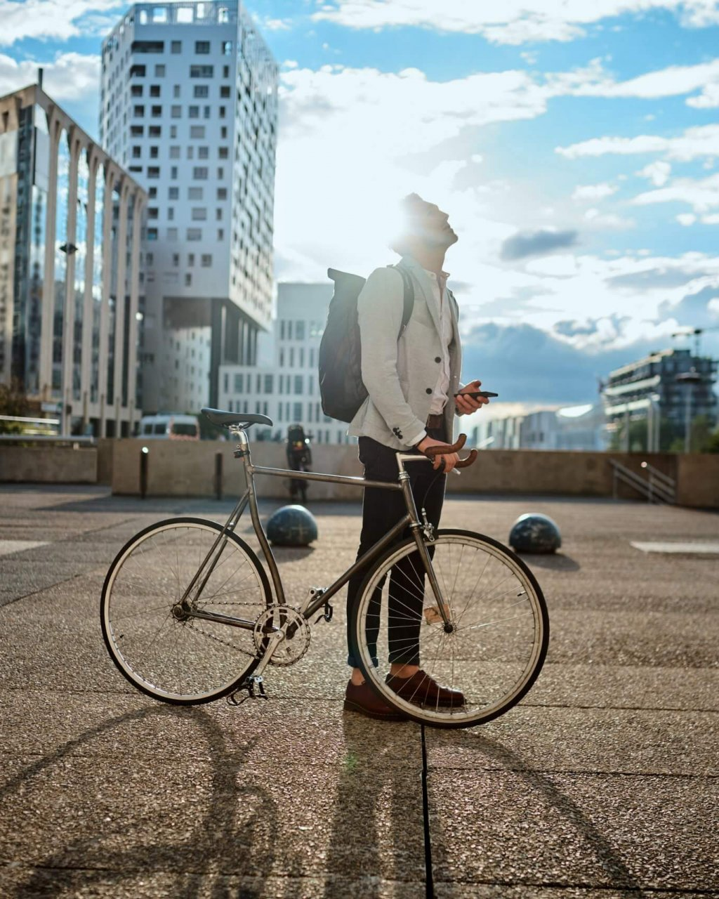 Shot of a young businessman using a smartphone while traveling through the city with his bicycle